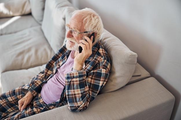 Мужчина с короткими седыми волосами звонит по мобильному телефону