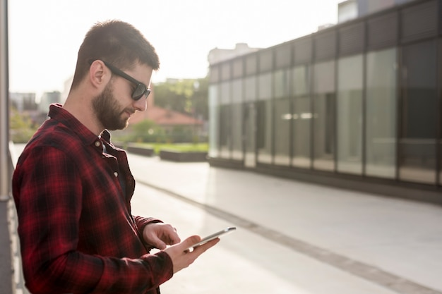 Male with sunglasses using smartphone
