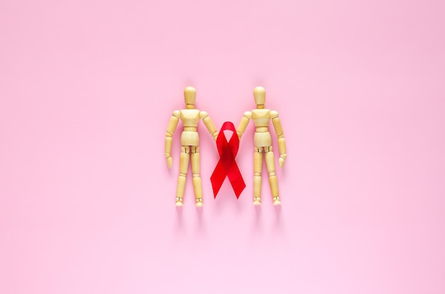 Male wooden model holding red ribbon for minimal safe sex world sexual health and aids day concept