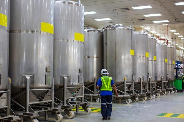 垂直スクロールホイールステンレス鋼タンク工場での男性の作業検査プロセス化学セラー