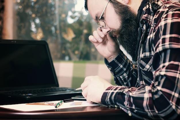 수염 난 남성 작업 노트북
