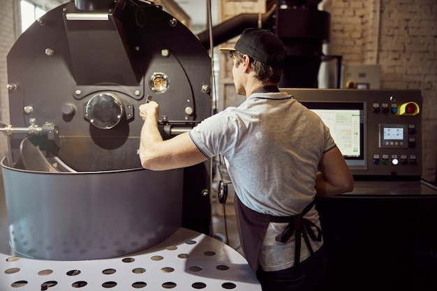 Male worker in apron operating professional equipment for roasting coffee beans while standing by control panel