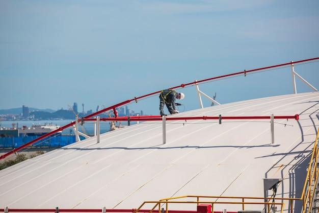 男性労働者は、貯蔵タンクの超音波厚さルーフプレートドームトップを検査するためのものです。