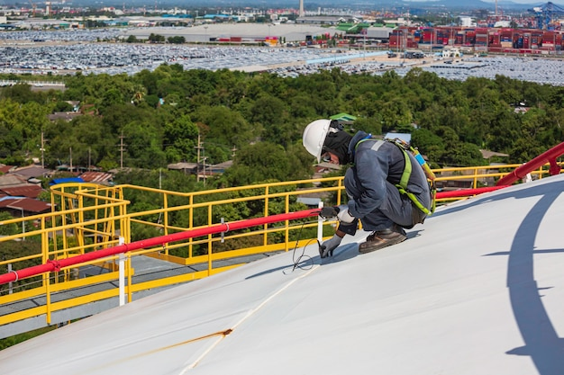 Male worker are for inspection ultrasonic thickness roof plate dome top of storage tank.