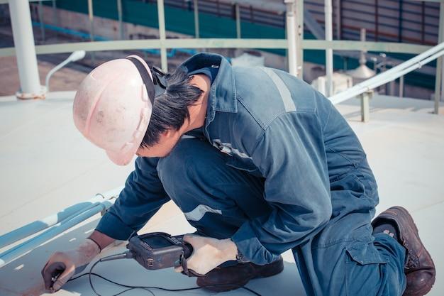 남성 작업자는 검사 배경 다리를 위한 저장 탱크의 초음파 두께 지붕입니다.