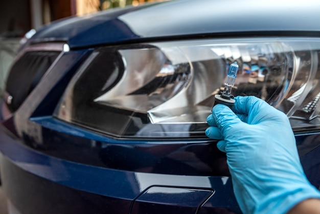 Male worker changes light bulb in the headlight, auto repair and service concept