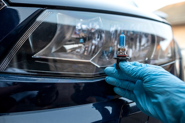 남자 직원은 헤드라이트, 자동차 수리 및 서비스 개념에서 전구를 변경합니다.