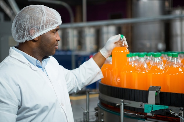 Male worker checking juice bottles in factory