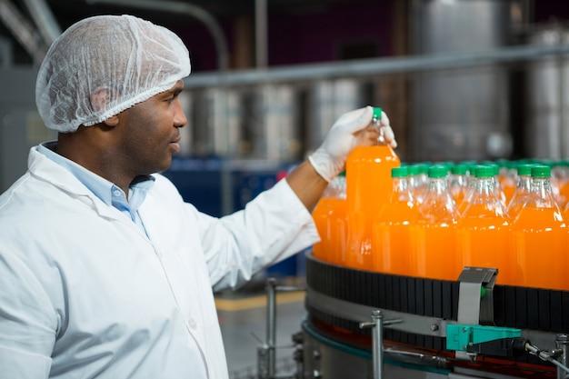 Lavoratore di sesso maschile che controlla le bottiglie di succo in fabbrica