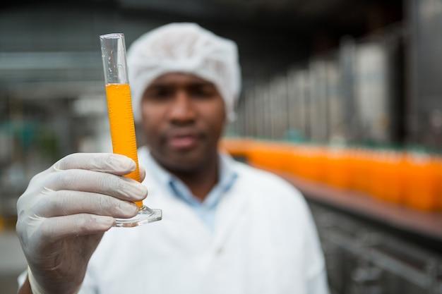 Operaio maschio che controlla il succo in fabbrica