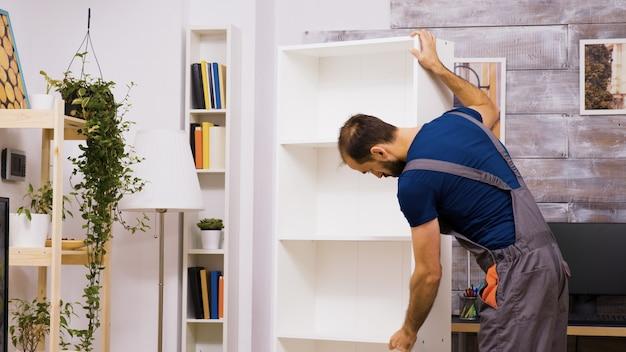 Lavoratore maschio che controlla nuovi mobili dopo l'assemblaggio tuttofare che aiuta le persone.