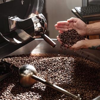갓 볶은 커피 콩의 품질을 확인하는 남성 노동자