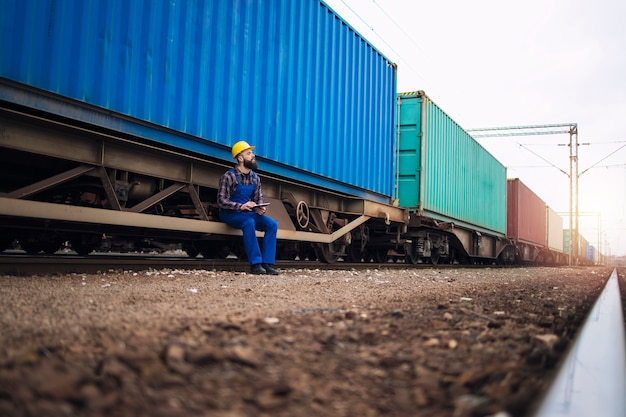 Male worker checking train trailers with shipping containers before departure