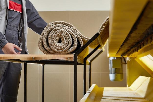 ランドリールームの自動洗濯機設備と乾燥機でカーペットを掃除する男性労働者