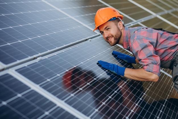 Работник мужского пола, чистящий солнечные батареи