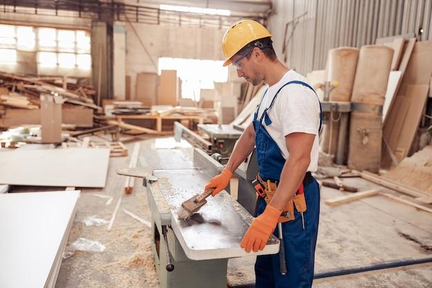 작업장에서 목공 기계를 청소하는 남성 노동자 프리미엄 사진