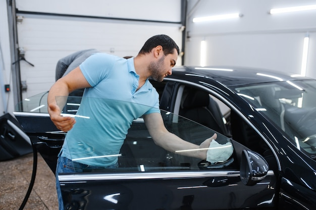 男性労働者は、着色、チューニングサービスのために車を掃除します。ガレージの車の窓にビニールの色合いを塗る整備士、色付きの自動車ガラス