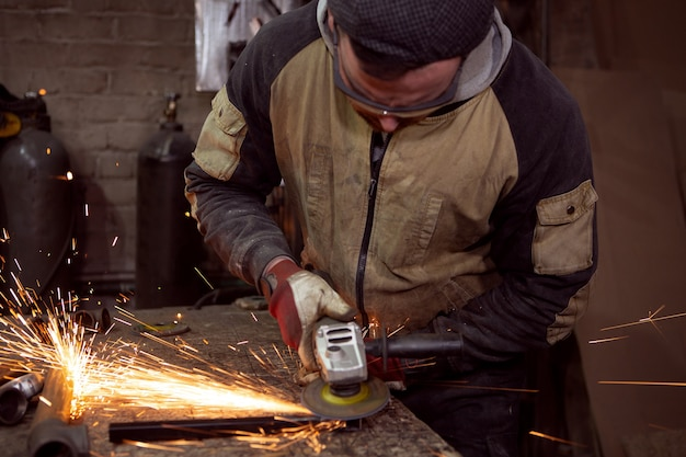 A male worker cuts metal with a hand grinder, bright sparks fly from under the saw in all directions.