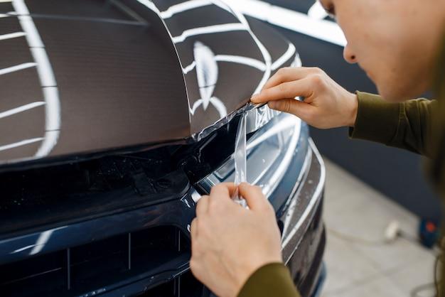 男性労働者が車のボンネットの透明な保護フィルムをカットします。自動車の塗装を傷から保護するコーティングの設置。ガレージの新車、チューニング手順