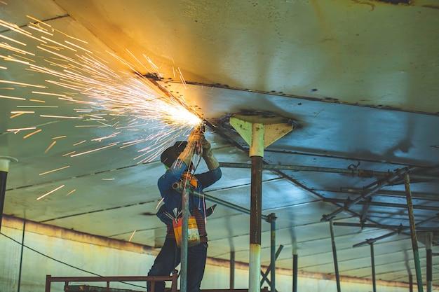 屋根の頭上の金属アークを切断する男性労働者は、限られたスペース内の機械タンクノズルアーク建設石油およびガス貯蔵タンクの一部です。