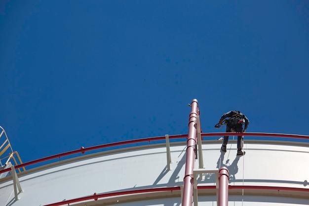 남성 작업자 다운 높이 탱크 쉘 플레이트 로프 사다리 액세스 두께 저장 탱크 가스 프로판의 안전 검사.
