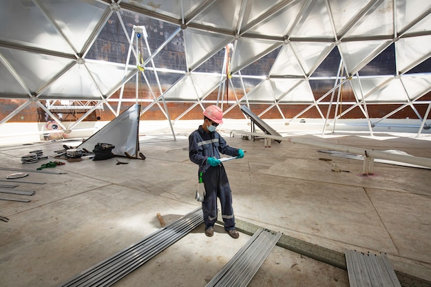 Мужской рабочий файл записи визуального осмотра резервуара в замкнутом пространстве является ограниченное пространство алюминия купола крыши освещения.