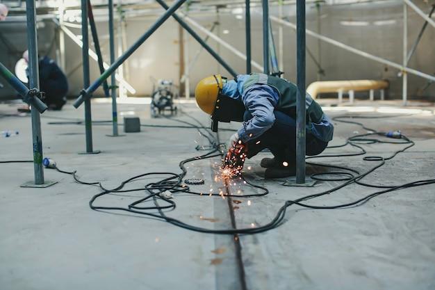 Мужчина-работник шлифует стальную пластину со вспышкой искр крупным планом в замкнутых пространствах.