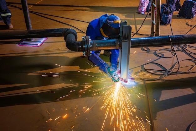 Мужчина-работник шлифует стальную пластину со вспышкой искр крупным планом, носить защитные перчатки, масло в замкнутых пространствах.