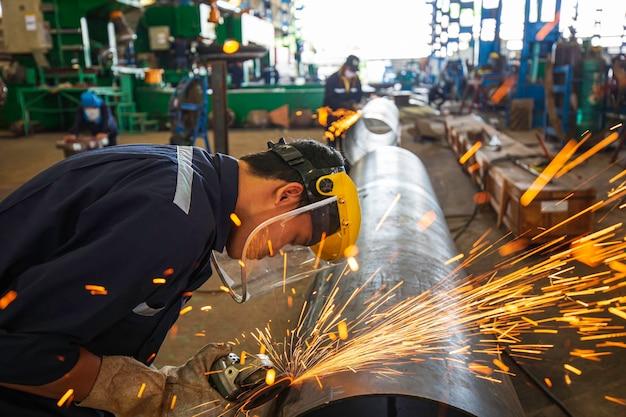 Мужчина-рабочий шлифует стальную пластину со вспышкой искр крупным планом в защитных перчатках