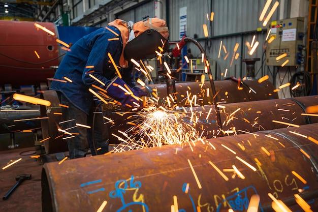 Рабочие-мужчины используют искры для шлифования труб с помощью электрического круга внутри промышленного строительства.