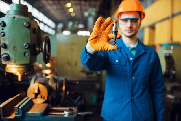 Male worker hands holds detail, lathe. plant. industrial production, metalwork engineering, power machines manufacturing