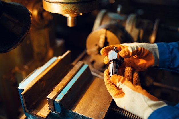 Male worker hands holds detail, lathe, plant. industrial production, metalwork engineering, power machines manufacturing
