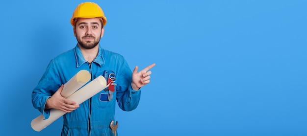 Male worker holding blueprints and pointing aside with index finger, unshaven engineer wearing yellow helmet and blue uniform