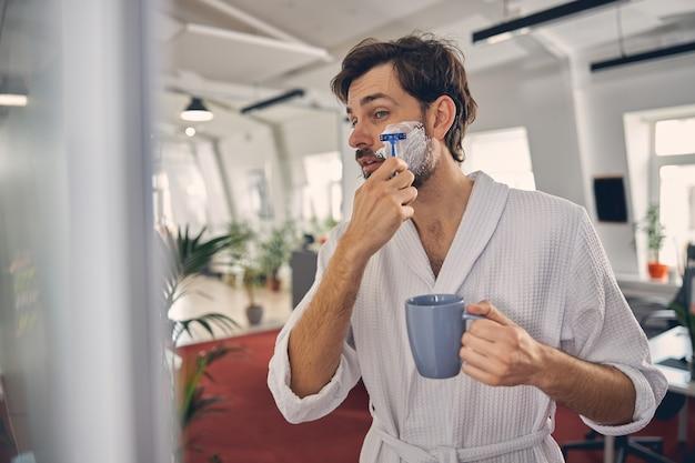 Мужчина-работник держит чашку кофе и удаляет волосы на лице бритвой в офисе