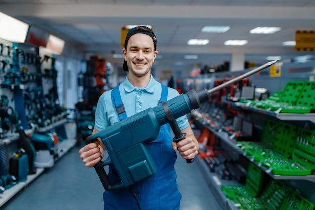 남성 노동자는 도구 저장소에 큰 전기 천공기를 보유하고 있습니다. 하드웨어 상점, 전기 기기 슈퍼마켓의 전문 장비 선택