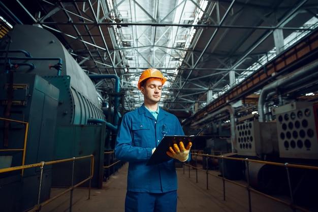 남성 노동자는 노트북, 공장 내부, 공장을 보유하고 있습니다. 산업 생산, 금속 공학, 동력 기계 제조