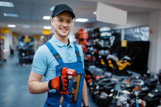 男性労働者が工具店で空気圧釘打機を保持しています。