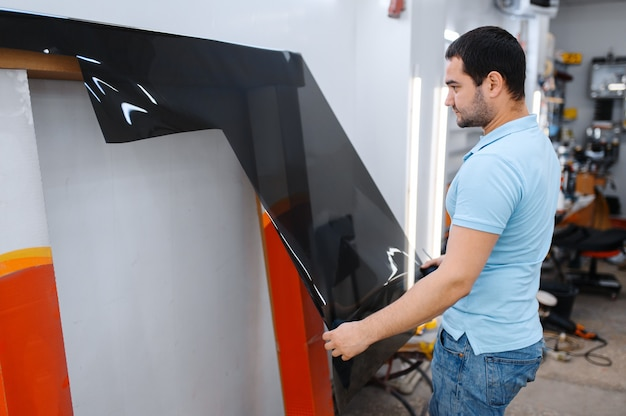 Male worker holds roll of car tinting, tuning service. mechanic applying vinyl tint on vehicle window in garage, tinted automobile glass