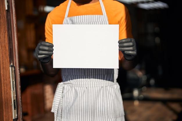 빈 카드 템플릿을 들고 앞치마 남성 노동자
