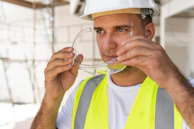 Работник-мужчина в строительстве, носить защитное снаряжение
