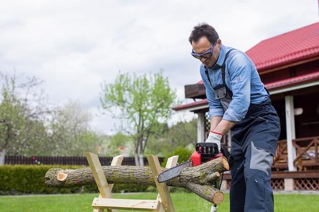 작업 바지에있는 남성 노동자는 전기 톱으로 안뜰에있는 sawhorses에 나무를 보았다