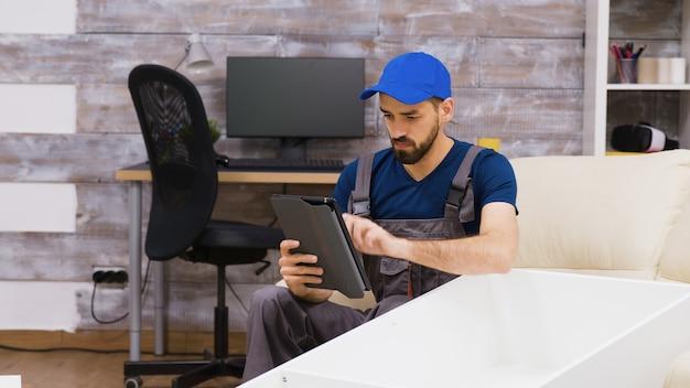 태블릿 컴퓨터에서 가구 조립품을 읽는 모자를 쓴 작업복을 입은 남성 노동자.