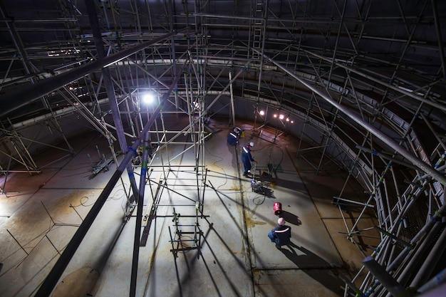 限られたスペースで進行中の男性労働者タンクオイル検査足場