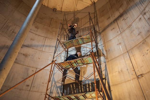 限られたスペースで進行中の男性労働者タンクステンレス油検査足場