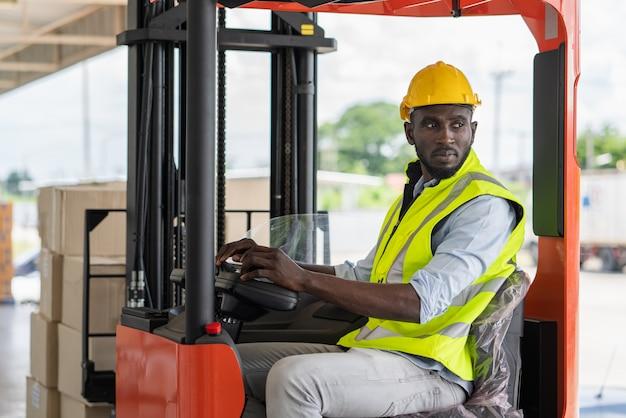 Работник-мужчина в жилете безопасности и шлеме за рулем вилочного погрузчика
