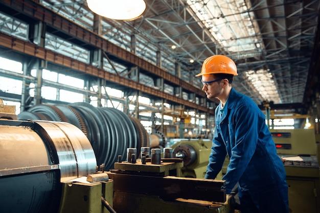 유니폼과 헬멧을 입은 남성 노동자가 공장에서 선반을 돌고 있는지 확인합니다. 산업 생산, 금속 공학, 동력 기계 제조