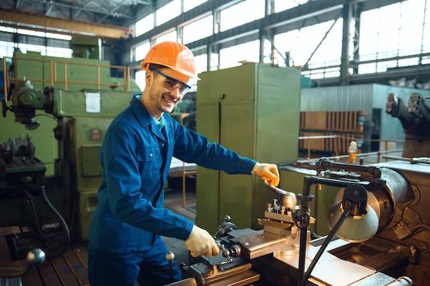 Мужчина в форме и шлеме проверяет токарный станок на заводе