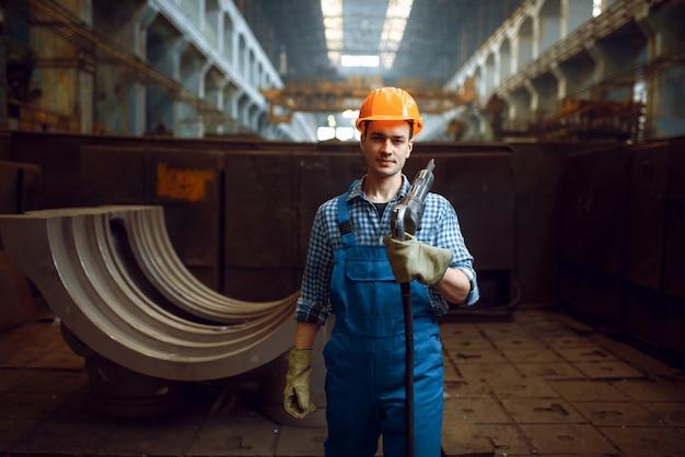 制服とヘルメットの男性労働者は、工場で空気圧削岩機を保持しています。金属加工産業、鉄鋼製品の工業製造
