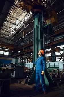 제복을 입고 헬멧을 쓴 남성 노동자가 공장에서 크레인을 작동합니다. 산업 생산, 금속 공학, 동력 기계 제조