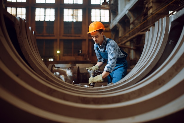 Рабочий в форме и шлеме снимает окалину с металлических деталей на заводе. металлообрабатывающая промышленность, промышленное производство металлопродукции